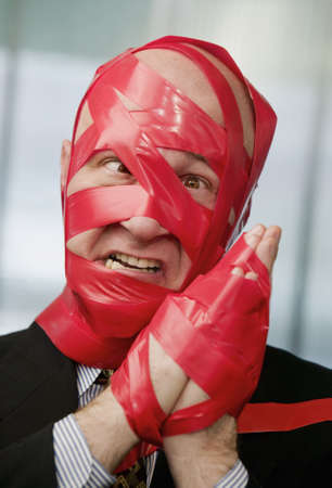 hindrance: Cross-eyed businessman wrapped in red tape