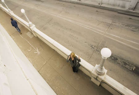 sidewalk talk: Wide shot from above of  woman on her cell phone next to an empty road. Stock Photo