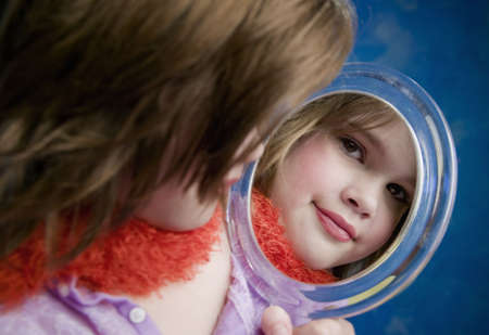 Little Girl Playing Dress-Up Looking in a Handheld Mirror Stock Photo