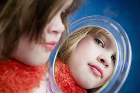 dressup: Little Girl Playing Dress-Up Looking in a Handheld Mirror Stock Photo