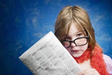 Young Girl Dressed Up in Reading Glasses Reading a Newspaper