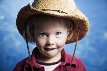 Little girl in front of blue wall wearing a cowboy hat with her tongue out