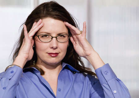 harried: Mildly Frustrated Business Woman with her Hands at her Temples
