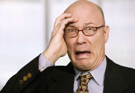 Horrified businessman with a hand to his forehead photo