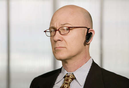 handsfree phone: Portrait of businessman with a hands-free phone in his ear