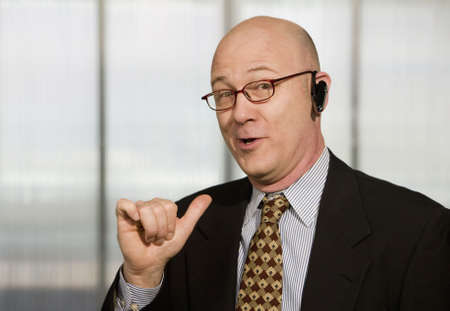 handsfree phone: Portrait of businessman with hands-free phone in his ear making a hand gesture