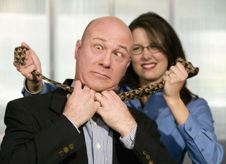 choke: Businesswoman strangles a male coworker with his necktie Stock Photo