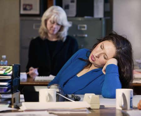 Hispanic woman sleeps at her office desk photo