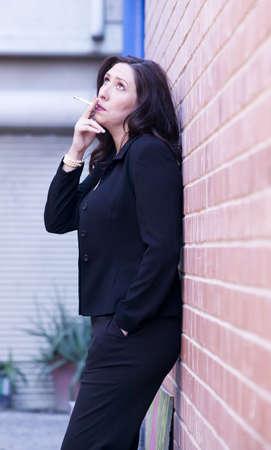 Hispanic woman in an alley smoking a cigarette