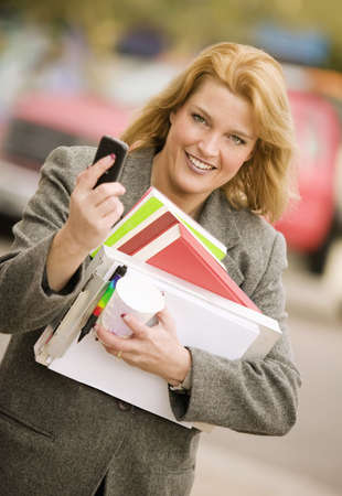 sidewalk talk: Pretty smiling woman with a cell phone and books walking in an urban setting