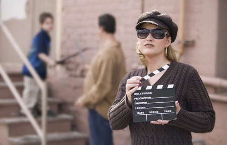 Woman holding a film slate in front of a man and boy photo