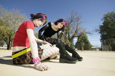Two Punk Girls Sitting on a cement playground photo