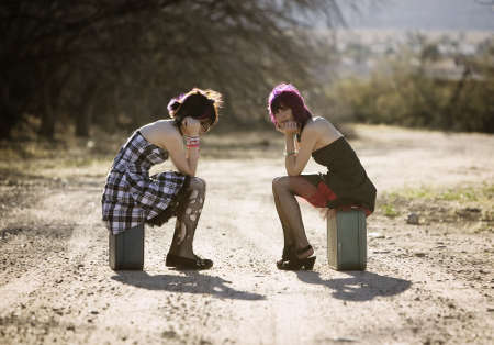 Two punk women sitting on suitcases and waiting on a rural road photo