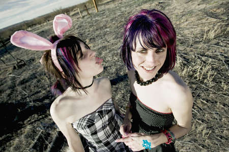 emo: Punk girl sticking her tongue out at her friend Stock Photo