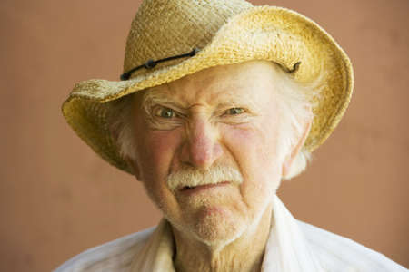confrontational: Senior Citizen Man Frowning n a Straw Cowboy Hat Stock Photo