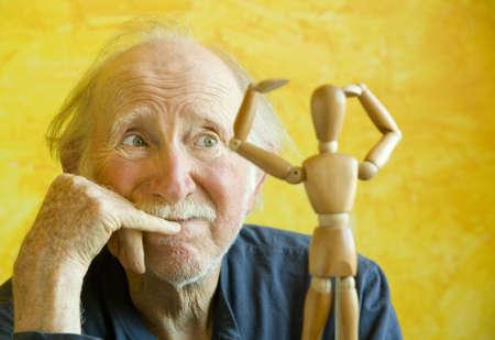 Elderly Artist Ponders a Wooden Figure Model