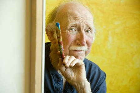 Elderly painter working on a large canvas