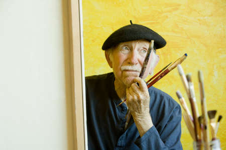 Elderly painter wearing a beret working on a large canvas Фото со стока