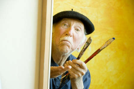 Elderly painter wearing a beret working on a large canvas and looking up