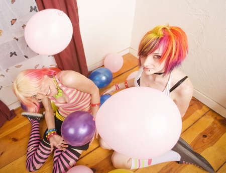Two punk girls in a room with colorful balloons