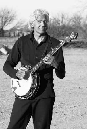Banjo player with his instrument in a rural setting Stock Photo - 3121657