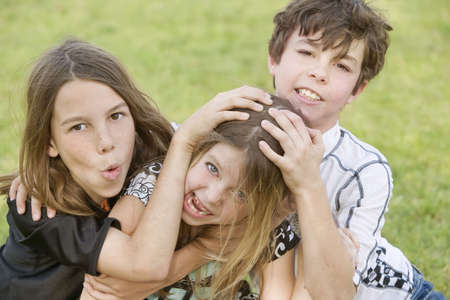 Three young siblings wrestling outdoors on the grass Stock Photo