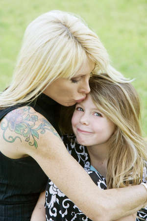 Pretty mom hugs and kisses her cute freckle-faced daughter