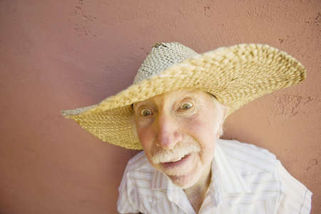 scared man: Senior Citizen Man with a Funny Expression Wearing a Straw Cowboy Hat
