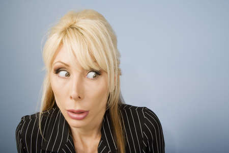 apprehensive: Close Up of an Apprehensive blonde businesswoman in front of a blue background
