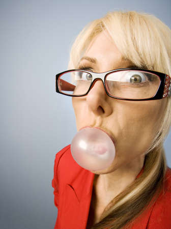 pucker: Woman in red with glasses blowing a bubble