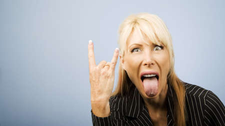 Businesswoman in a pinstripe suit making a bull horns sign