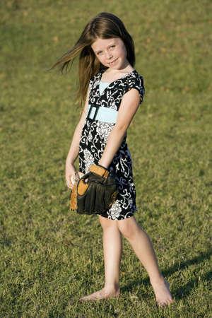 Schattig meisje in de zomer jurk met een honkbal Stockfoto