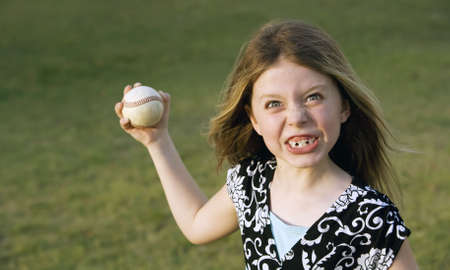 Cute young girl in summer dress with a baseball photo