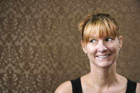 Pretty woman smiling in front of a gold-flocked wallpaper background Stock Photo - 3254139