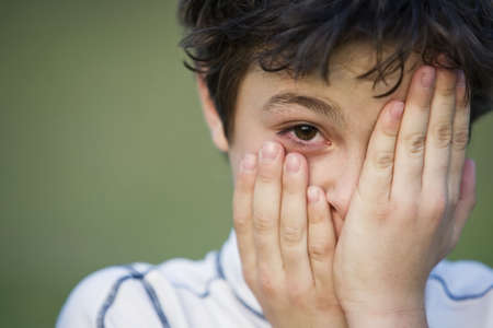 Portrait of a Young Teen Boy with Dark Curly Hair Covering His face