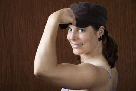 Closeup of woman with blue eyes wearing a cap flexing her bicep Stock Photo - 3264407