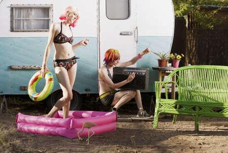 Women doing summer activities outside a travel trailer Stock Photo