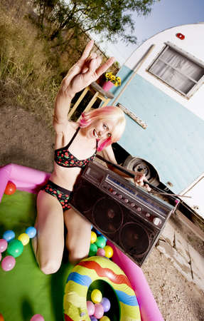 Woman with a boom box in an inflatable play pool photo