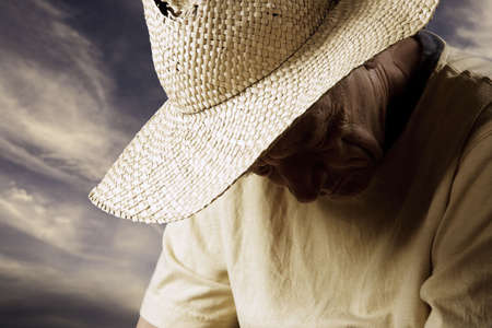 Senior Man in a Straw Hat with his Head Down Stock Photo