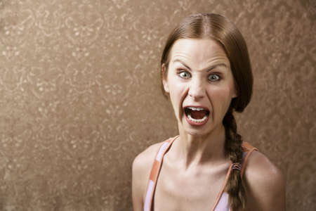 enraged: Screaming Young Woman in front of Gold wallpaper