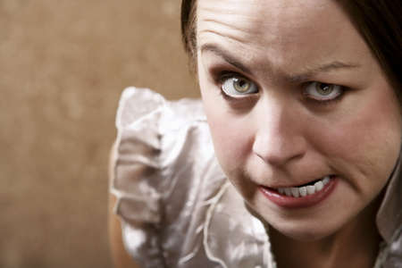 exasperation: Young woman making stern face in front of a gold wallpaper background Stock Photo