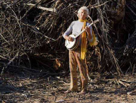 Barefoot banjo Player in Fraont of a Big Pile of Wood photo