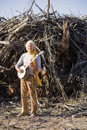 Barefoot banjo Player in Front of a Big Pile of Wood photo