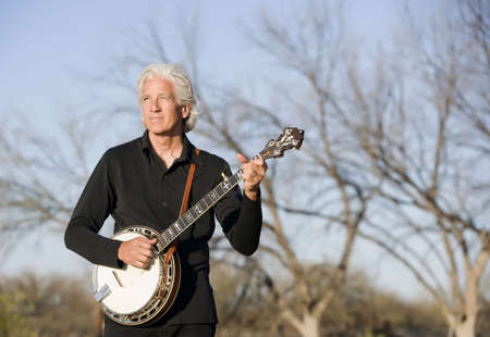 Banjo Player in Front of a Bare Trees photo