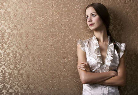 wallflower: Pretty young woman waiting leaning up against a wall with gold wallpaper Stock Photo