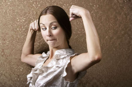 flexed: Pretty Young Woman Admiring Her Flexed Biceps Stock Photo
