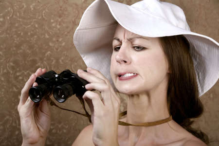Young Woman with Sunglasses and a Floppy White Hat Looking through the Wrong End of Binoculars
