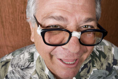 dweeb: Silly Mexican-Italian Man with Taped Corrective Glasses Stock Photo