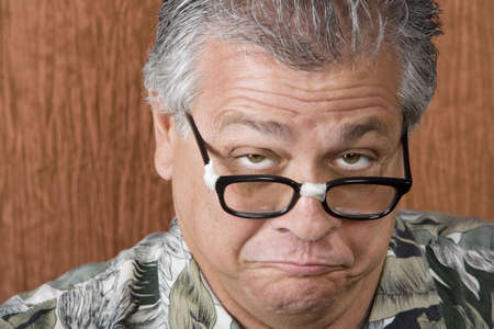 glum: Silly Mexican-Italian Man with Taped Corrective Glasses Stock Photo