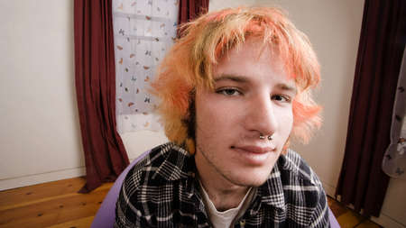 pierce: Closeup of a Young man with Bright Hair in a Bare Room